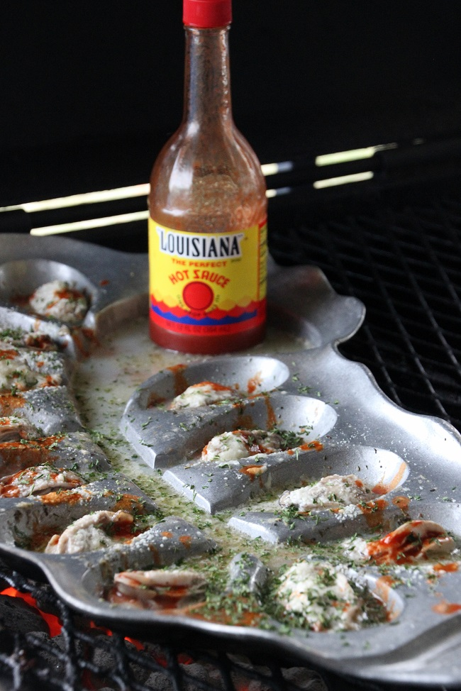 Grilling Shucked Oysters on The Oyster Bed, seasoned with Louisiana Hot Sauce