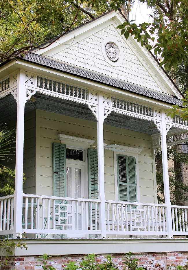 Two bay shotgun raised cottage with Haint Blue porch ceiling and louvered shutters, located in historic Old Mandeville, Louisiana. It has a gabled front with decorative shingles and a porch on two sides, considered as 'Louisiana Northshore Style' or 'Abita Style'