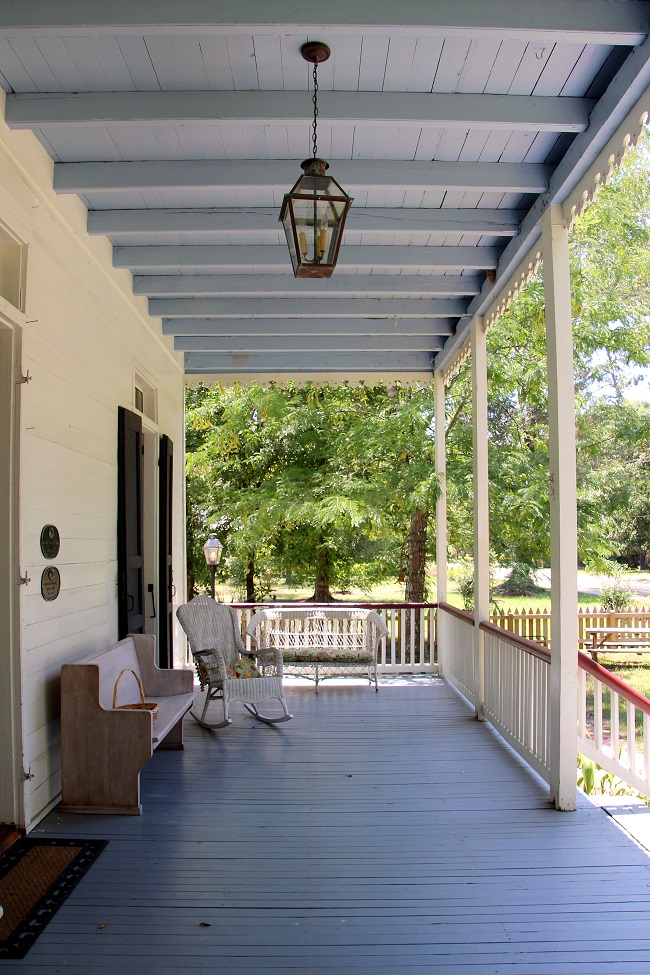 Jean Baptiste Lang House, circa 1850, in historic Old Mandeville. The Anglo-Creole Cottage has a Haint Blue porch ceiling, Bevolo French Quarter style lantern light fixture, French Quarter Green shutters, and a cypress wood church pew bench with wicker chairs on the raised porch