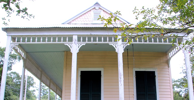 Haint Blue porch ceiling on a two bay shotgun raised cottage house in Abita Springs Historic District.  The gabled front porch with decorative shingles and porch on two sides is typical of the style of Abita architecture, considered 'Louisiana North Shore' or 'Abita Style'