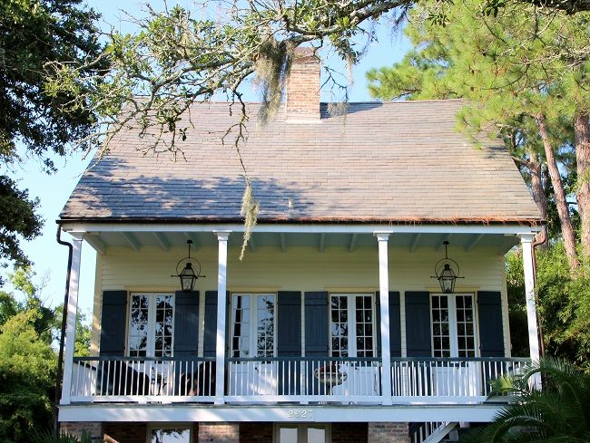 Raised Creole Cottage listed on the National Register of Historic Places in Old Mandeville, LA, has a Haint Blue porch ceiling, French Quarter Green shutters, and Bevolo gas lanterns