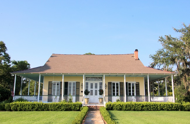 Little Flower Villa, circa 1836, on Lakeshore Drive in historic district of old Mandeville, LA. The restored Southern Creole style house has a Haint Blue porch ceiling, French Quarter Green horizontal slat shutters, and Bevolo gas lanterns.