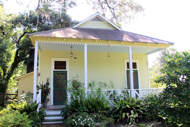 Two bay shotgun double raised cottage with a Haint Blue porch ceiling, located in the Abita Springs Historic District