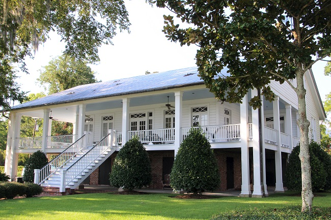 Windhaven House, circa 1926, on Lakeshore Drive in Old Mandeville, LA, has a Haint Blue porch ceiling, French doors with transoms, and is referred to as a 'Center Hall' home