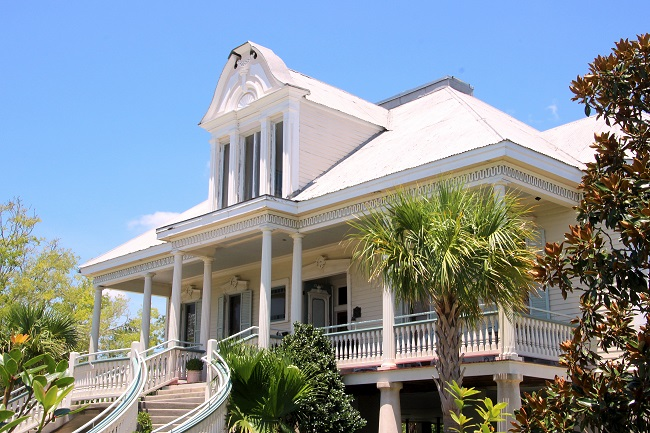 Justine Plantation, originally built in Centreville, Louisiana, in St. Mary Parish during the early 1800's, was moved by barge to the New Orleans Northshore on the lakefront of Old Mandeville in 2003. The prominent dormer and neoclassic detailing were added in 1907. The Haint Blue porch ceiling color compliments the other colors of the raised Antebellum house.