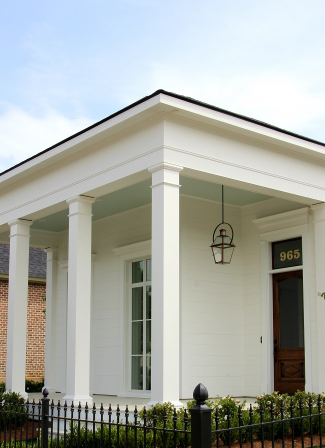 Contemporary home, built by J Hand Homes, with Haint Blue porch ceiling, stained antique wood front door with transom, and Bevolo French Quarter style gas lantern