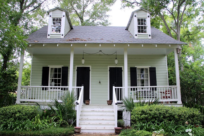 Historic double shotgun raised cottage with Haint Blue porch ceiling, French Quarter Green shutters, and dormers on the roof, in Old Mandeville, LA