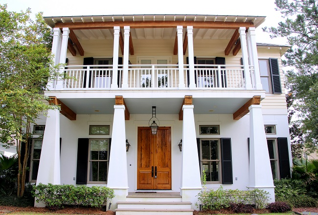Southern Living Louisiana Idea House, Bayou Bend, in TerraBella Village has a Haint Blue porch ceiling, cypress wood front door, French Quarter Green horizontal louvered shutters, and Bevolo gas lantern.